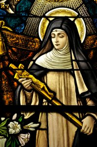 Stained Glass window of St Monica holding the cross of Jesus Christ in peaceful prayer